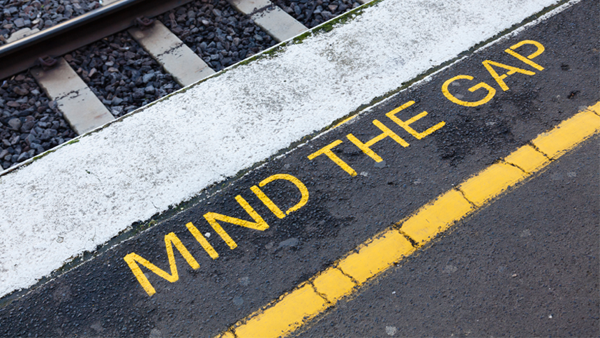 train stop with sign that reads mind the gap