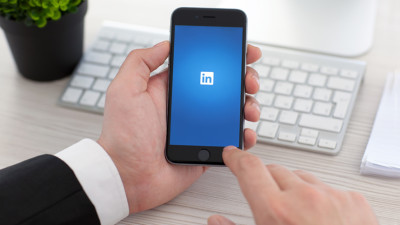 professional using LinkedIn on smartphone