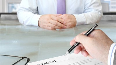 interviewer inspecting resume with red flags