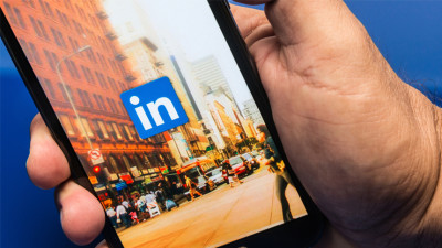 hand holding phone with Linkedin app opened