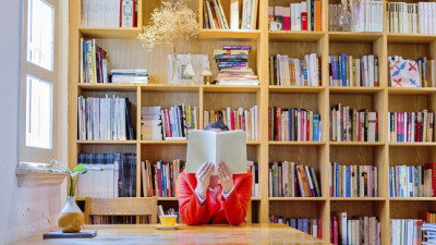 Woman reading a book in library.