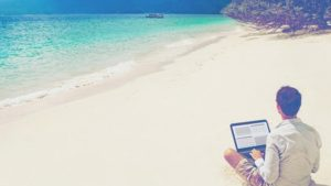 man on beach laptop
