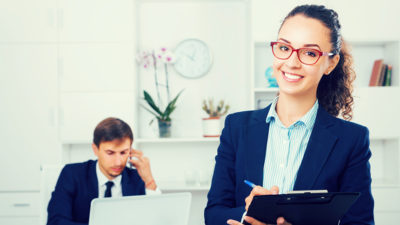 young woman manager holding clipboard in office