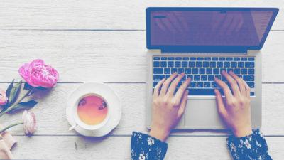 woman typing laptop tea flowers